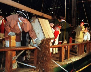Historical reenactors pour chests of tea into Boston Harbor