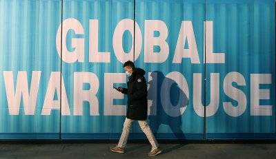 Man Walks Past International Trade Market in Beijing, China