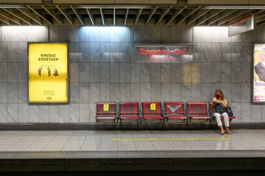 A Woman Waits for a Subway Near a COVID-19 sign in Athens, Greece