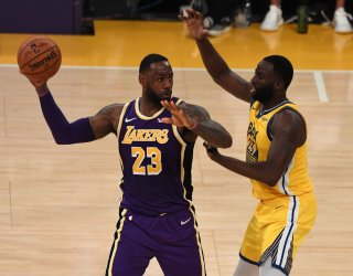 Lakers forward LeBron James (L) fights off Warriors forward Draymond Green in third quarter action at Staples Center