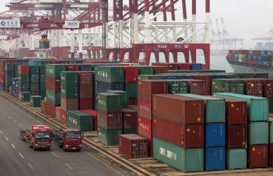 Trucks deliver containers to designated areas at the port in Qingdao, China