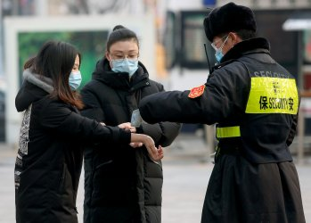A security guard checks the temperature of people in Beijing, China