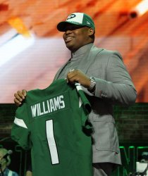 Quinnen Williams holds up his jersey with NFL Commissioner Roger Goodell