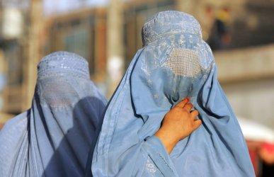 Women clad in burqas walk the streets in Herat