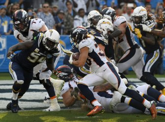 Broncos' running back Phillip Lindsay (30) scores a touchdown past Chargers' end Melvin Ingram III (54)