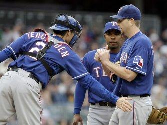 Texas Rangers starting pitcher Scott Feldman gets a tap from catcher Taylor Teagarden at Yankee Stadium in New York