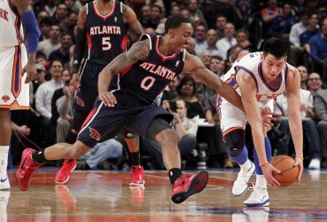 New York Knicks Jeremy Lin and Atlanta Hawks Jeff Teague reach for a loose ball at Madison Square Garden in New York