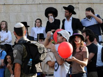 Secular Israelis hold balloons and blow bubbles during an Ultra-orthodox demonstration against the desecration of the Sabbath in Jerusalem