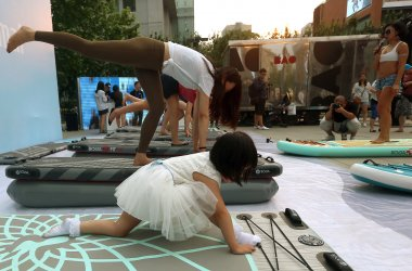 Chinese women take part in a free, public yoga class in Beijing, China