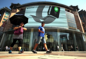 Chinese walk past one of Apple's main showrooms in Beijing