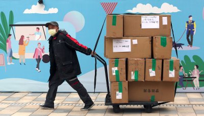 A delivery driver wearing a protective face mask hauls boxes in Beijing, China