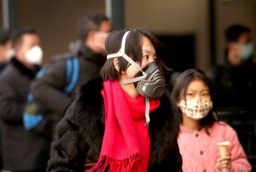 Chinese wear protective face masks at a train station in Beijing, China