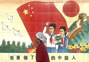 A Chinese worker walks past a government mural in Beijing, China