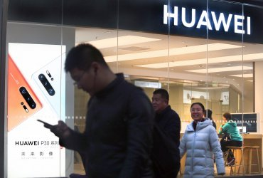 Chinese walk past a Huawei store in Beijing, China