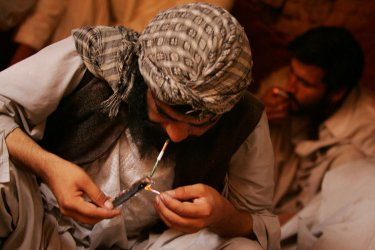 Heroin addicts smoke the drug in Afghanistan.
