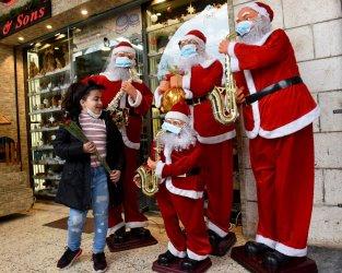 A Palestinian Girl Looks At Santas On Christmas Eve In Bethlehem