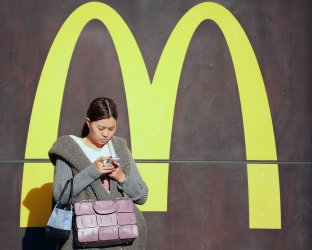 A Chinese woman stands in front of a McDonald's in Beijing