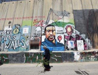A Palestinian Walks Past A Graffiti Mural Of George Floyd In Bethlehem, West Bank