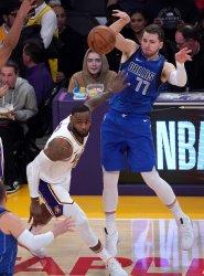 Dallas Mavericks Luka Doncic passes the ball past Los Angeles Lakers LeBron James