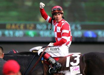 Jockey Jose Ortiz and Serengeti Empress celebrates winning the Kentucky Oaks