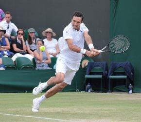 Mikhail Kukuskin returns in his fourth round match against Kei Nishikori at Wimbledon