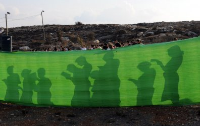 Israeli settler women pray during a protest in the illegal Jewish settlement Givat Asaf in the West Bank