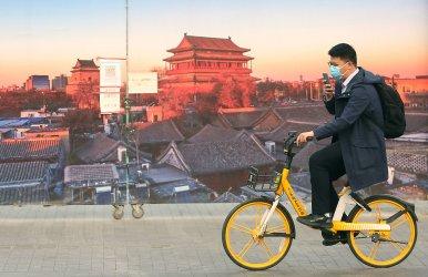 Businessman Rides Bike Past Photo of Beijing, China