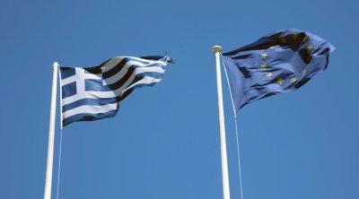 A Euro flag flies next to a Greek flag