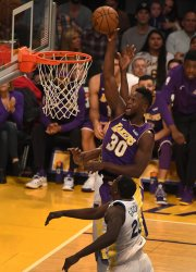 Lakers forward Julius Randle shores over Warriors Draymond Green in Los Angeles