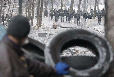 Ukrainian riot police stand near a barricade