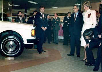 Princess Diana and Prince Charles admire a Rolls Royce placed on top of teacups
