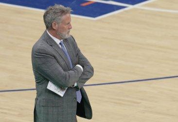 Philadelphia 76ers Brett Brown stands near the bench