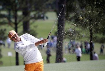 Rickie Fowler hits an iron at the Masters
