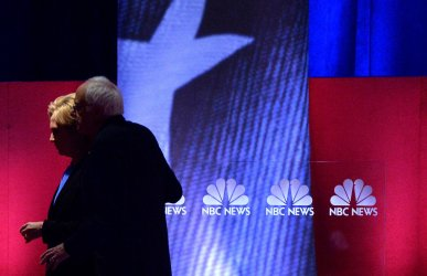 Democratic Presidential Candidates Clinton and Sanders walk on stage