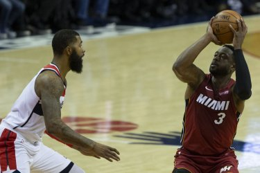 Heat guard Dwyane Wade shoots while guarded by Wizards forward Markieff Morris