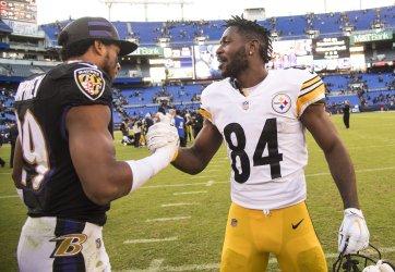 Steelers quarterback Ben Roethlisberger talks to Ravens quarterback Joe Flacco