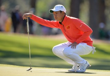 Cheng Jin lines up a putt at the Masters