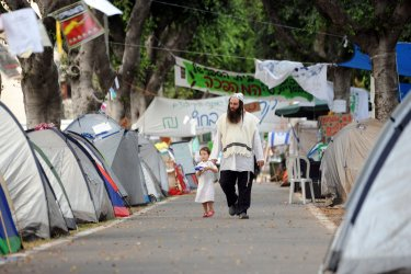 An Ultra-Orthodox Israeli walks in a Tel Aviv protest tent encampment against the high costs of living in Israel