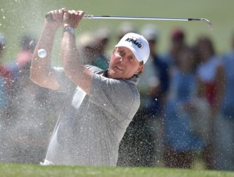 Phil Mickelson reacts after hitting a shot from the bunker