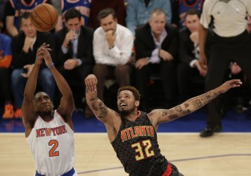 Hawks Mike Scott and Knicks Langston Galloway leap for a ball