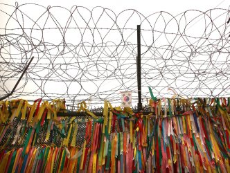 Ribbons of peace hang under barbed wire near the DMZ in Seoul