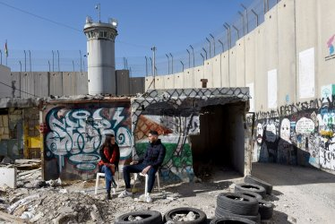 Tourists Sit Near Israel's Separation Wall In Bethlehem