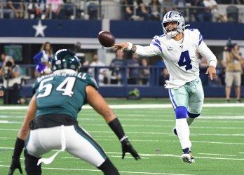 Dallas Cowboys quarterback Dak Prescott (4) flips the ball to Ezekiel Elliott