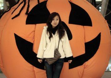 Woman has her photo taken in front of a Halloween display in Beijing.