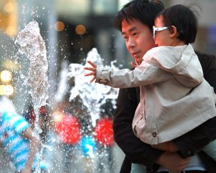 A Chinese boy enjoys a water fountain in Beijing