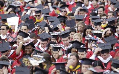 Graduates hold their graduation caps at Rutgers Graduation