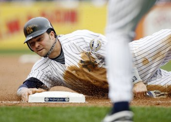 New York Yankees Nick Swisher dives into third base attempting to tag up in the fifth inning against the Boston Red Sox at Yankee Stadium in New York