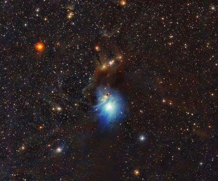 Newborn star bathes cosmic clouds in blue light