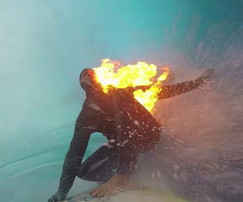 Professional surfer rides wave while on fire