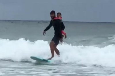 Chris Hemsworth surfs with daughter on his back in new video
